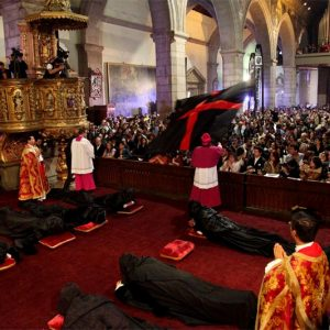 The priest waves the flag over the congregants during the Arrastre de Caudas